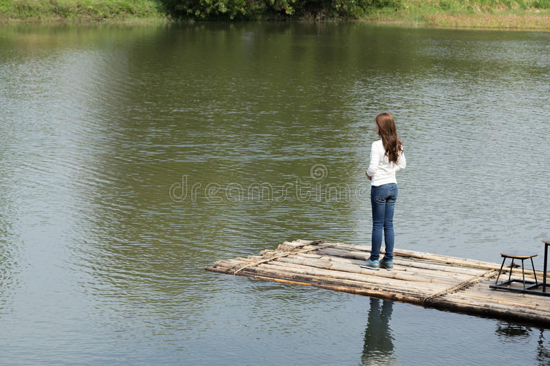 Woman on a bamboo raft in river. Woman on a bamboo raft in the river stock photo