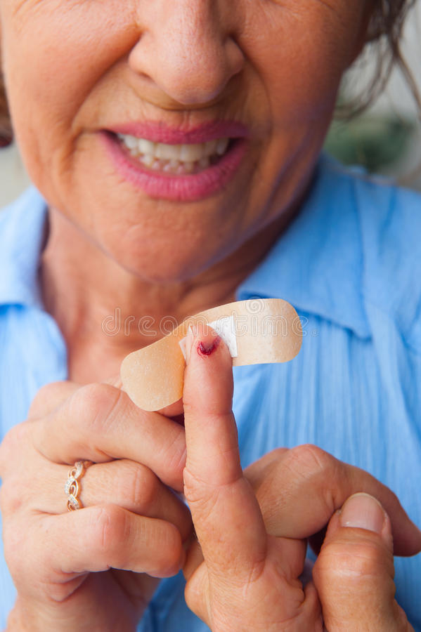 Woman band aid bloody finger wound. Portrait stressed mature woman in pain, suffering, close up of band aid on injured, cut bloody finger wound royalty free stock image