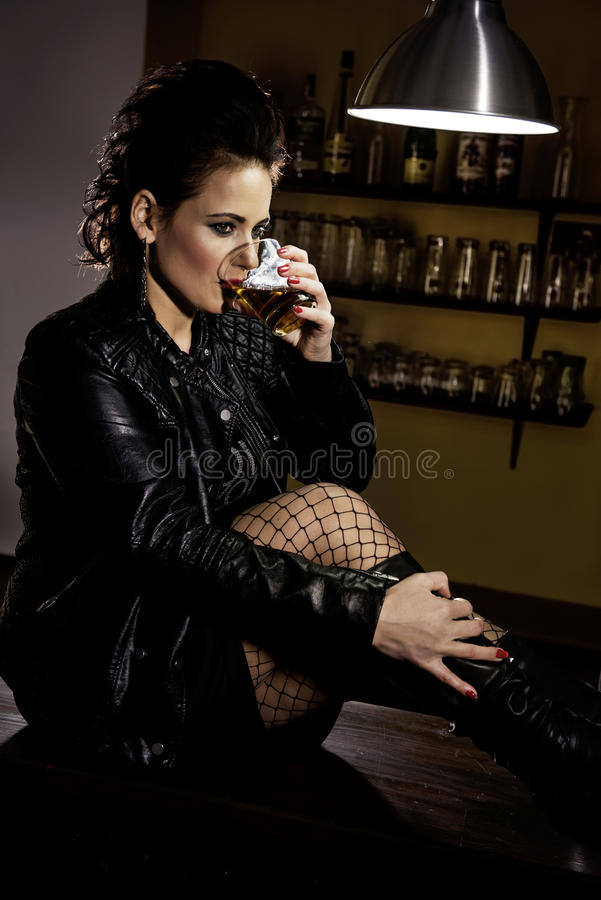 Woman in the bar. Woman dressed in black leather jacket sitting on the bar and drinking alcohol stock photos