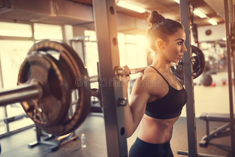 Woman with barbell in gym royalty free stock images