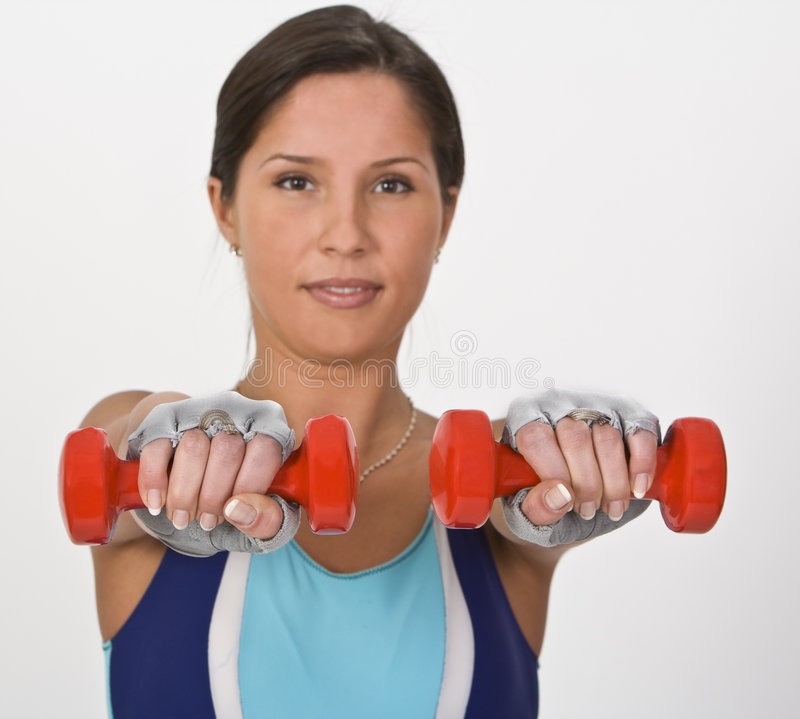 Woman with barbells. Image of a young woman doing barbells exercises,selective focus on the barbells. Take a look to my entire stock photos