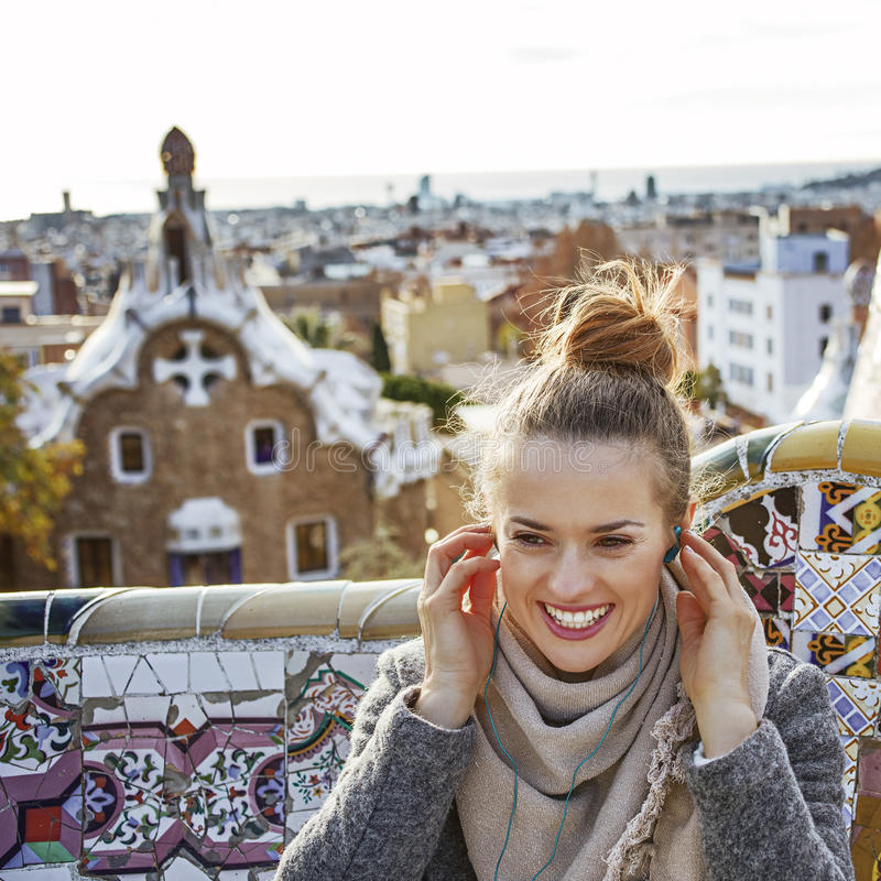 Woman in Barcelona listening audioguide while sitting on bench stock photo