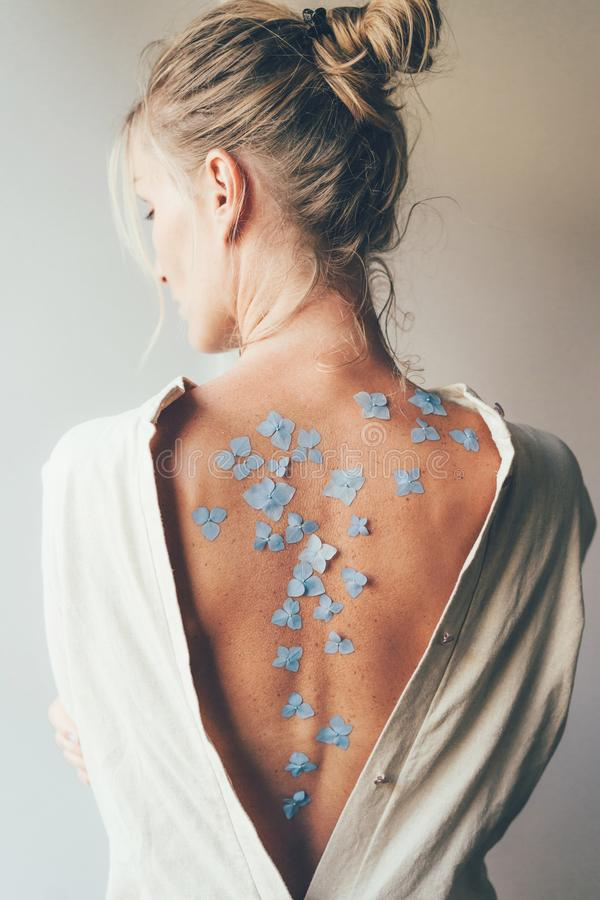 Woman with a bare back with flowers on the skin stock image