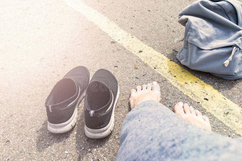 Woman with bare feet and backpack sitting on an asphalt road with a yellow single road line waiting vehicle for hitchhiking, royalty free stock photography