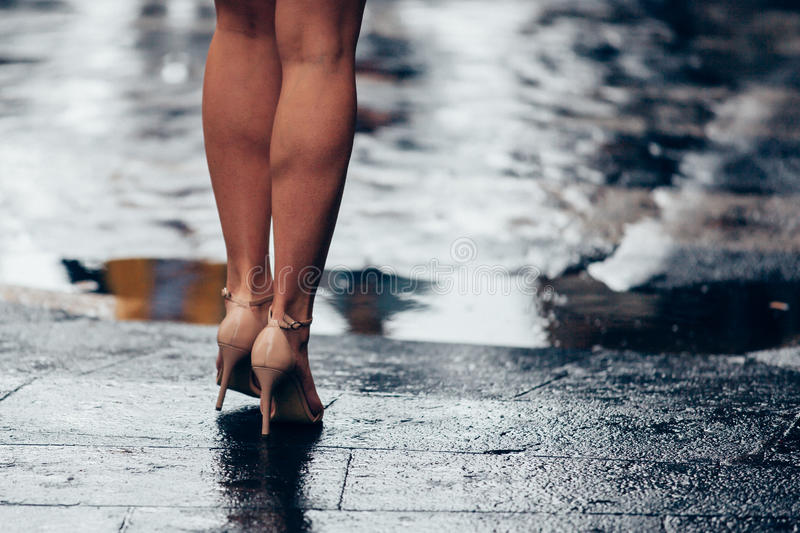 Woman in bare legs with heels in front of puddle royalty free stock image