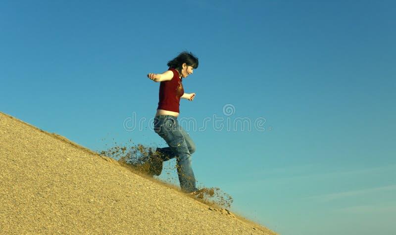 Woman barefoot running down a sand dune