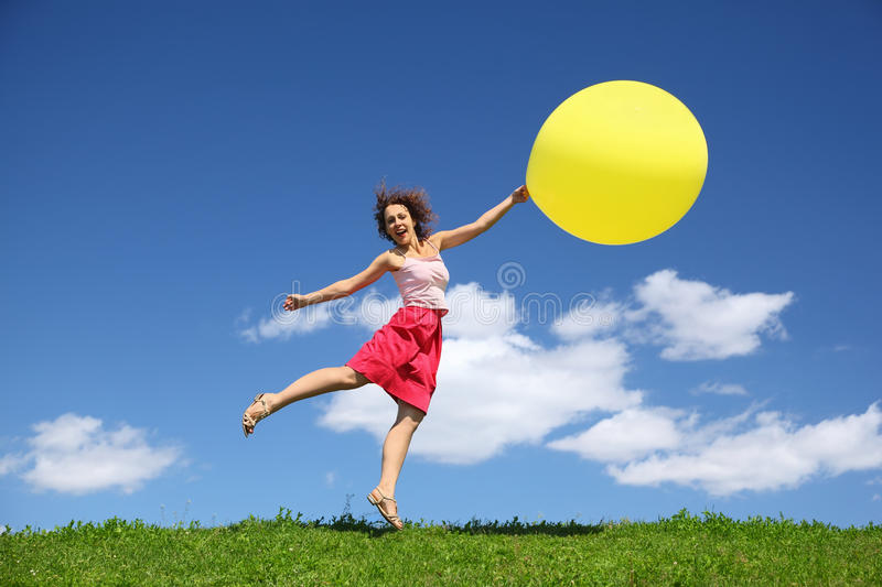 Woman barely touching earth flight away on balloon. Summer stock images