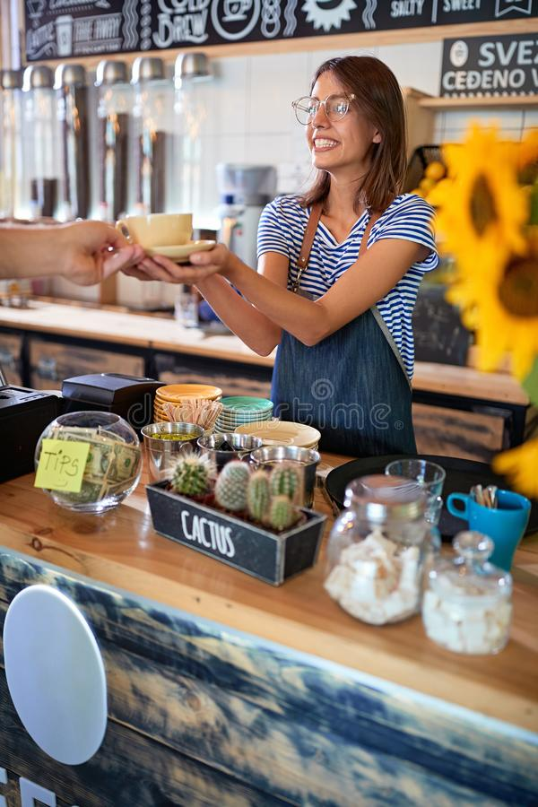 Woman barista making coffee and serving customer royalty free stock photography