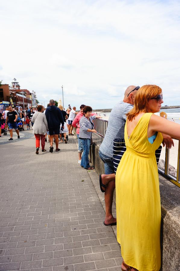 Woman by a barrier. Kolobrzeg, Poland - August 10, 2018: Woman in yellow dress and man standing by a barrier on the crowded promenade watching at the sea. This royalty free stock images
