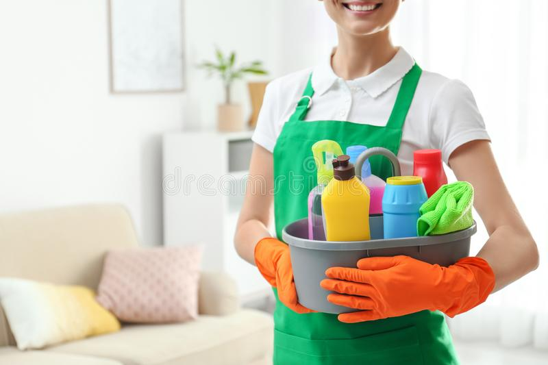 Woman with basin of detergents in living room. Cleaning service royalty free stock image