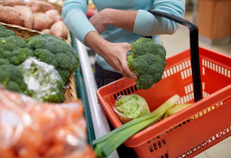 Woman with basket buying broccoli at grocery store. Sale, shopping, food, consumerism and people concept - woman with basket buying broccoli at grocery store stock photography