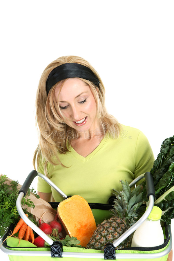 Woman with basket of food. A female holds a shopping bag filled with fresh fruit, vegetables, milk and bread royalty free stock photos