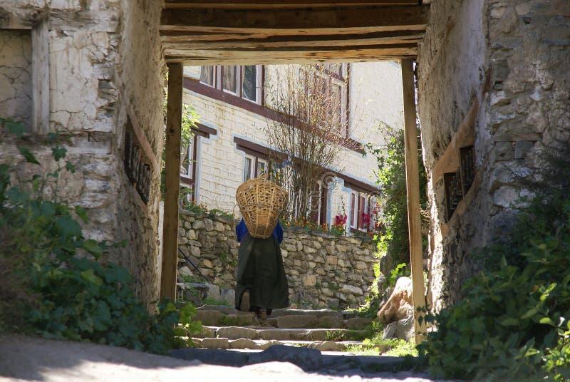 Woman with basket walks through gateway stock photos