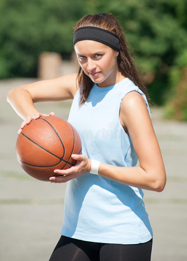 Woman with basketball. Young woman with basketball outdoors royalty free stock photography
