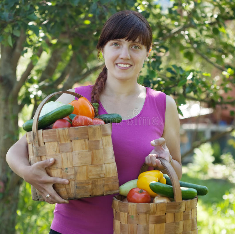 Woman with baskets of harvested vegetables royalty free stock image