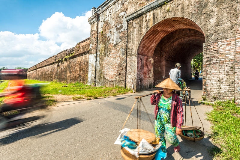 Woman with baskets in Hue city, Vietnam, Asia. Asian woman in traditional conical hat carrying baskets at Hue city citadel gates in Vietnam, Asia. Ancient royalty free stock image