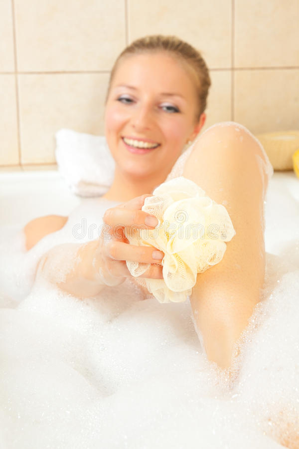 An attractive young woman lies in milk bath by Jovana