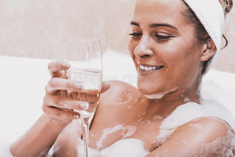 Woman in bath with champagne royalty free stock photography