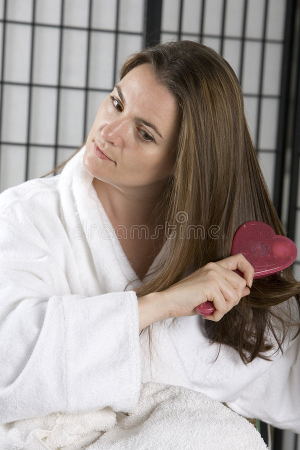 Woman in a bath robe brushing her hair stock images
