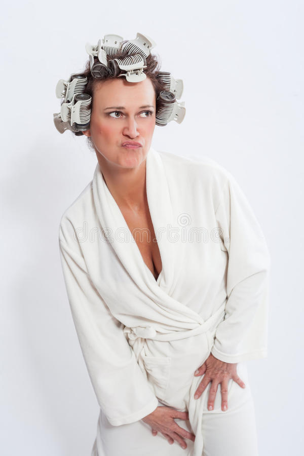 Woman in Bath Robe Posing with Pursed Lips. Humorous Three Quarter Length Portrait of Woman with Hair in Curlers Wearing White Bath Robe Standing with Pursed royalty free stock photo