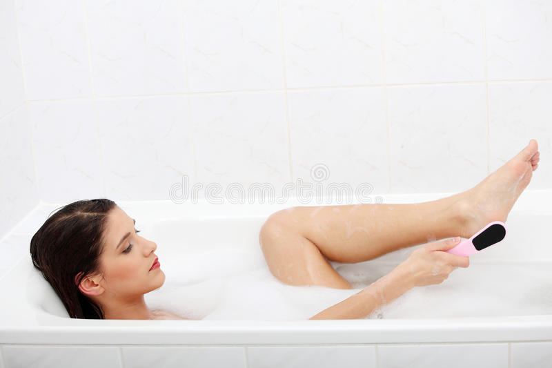 Woman in bath rubbing heel of foot. With brush for a pedicure royalty free stock photo