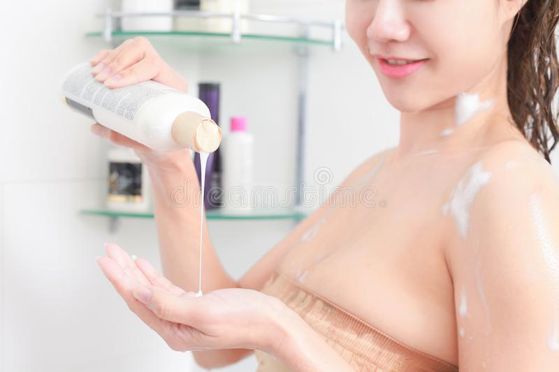 Woman in bath towel is applying cream on her hand while standing royalty free stock images