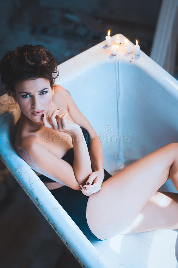 Woman in bath tub with candles stock image