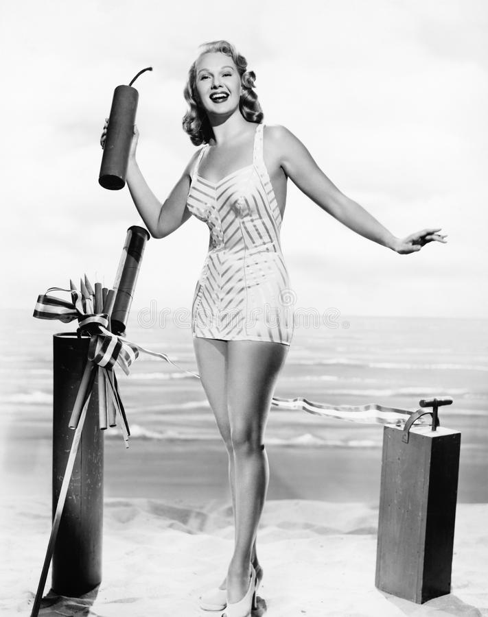 Woman in a bathing suit at the beach holding an oversized fire cracker in her hands. (All persons depicted are no longer living and no estate exists. Supplier stock photo