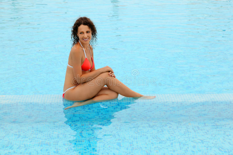Woman in bathing suit sitting in pool stock image