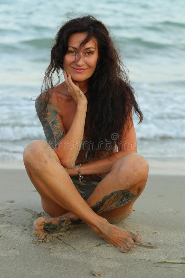 Woman in a bathing suit with tattooers against the backdrop royalty free stock photography