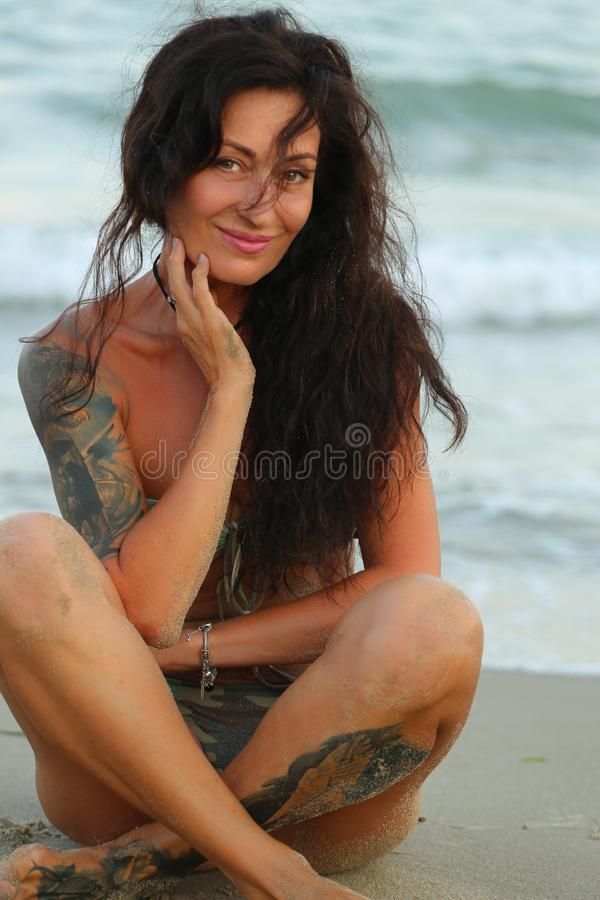 Woman in a bathing suit with tattooers against the backdrop royalty free stock images