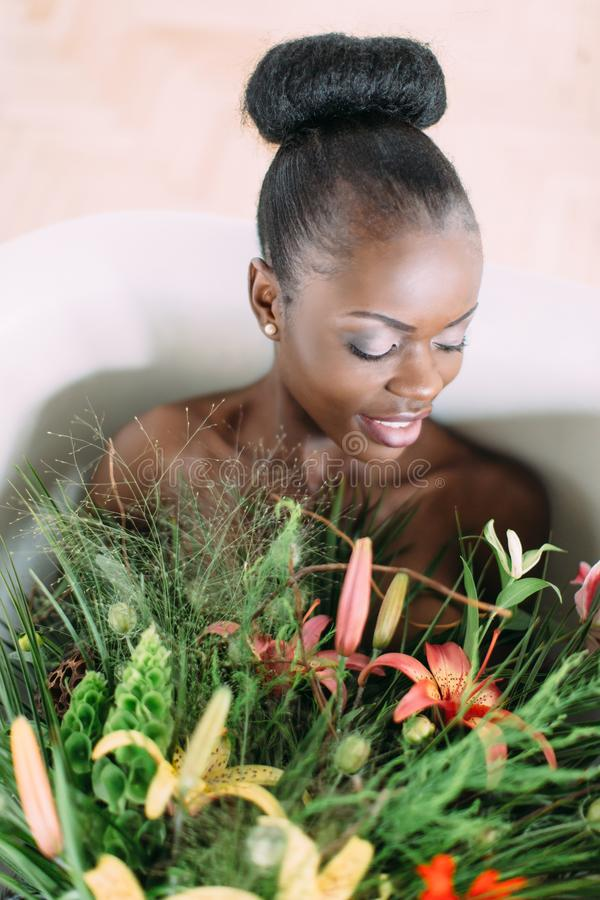 Woman bathing in a tub full of foam. Beautiful african american bride in decorated bath. Beautiful african american royalty free stock image