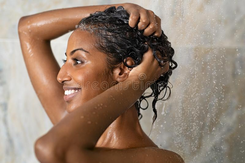Woman bathing and washing hair. Woman washing hair showering in bathroom at home. Smiling black woman bathing while looking away. Happy woman rinsing hair while royalty free stock images