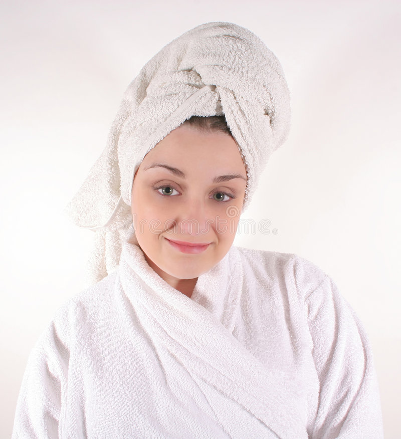 Woman in Bathrobe #2. A young green-eyed brunette wearing a bath robe and towel on her head royalty free stock photography