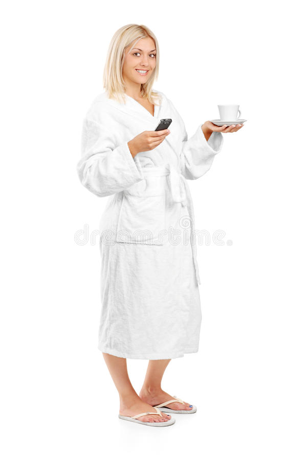 Woman In Bathrobe Holding A Coffee Cup And Phone Stock Images