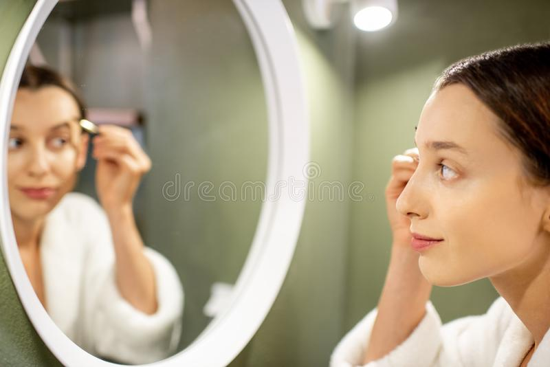 Woman painting eyebrows. Woman in bathrobe painting eyebrows near the round mirror on the green wall of the bathroom stock photo