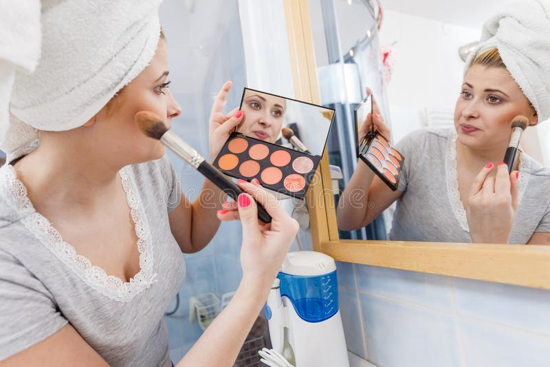 Woman in bathroom applying contour bronzer on brush. Contouring face kit, visage and make up concept. Woman in bathroom applying contour bronzer on cheekbones stock image