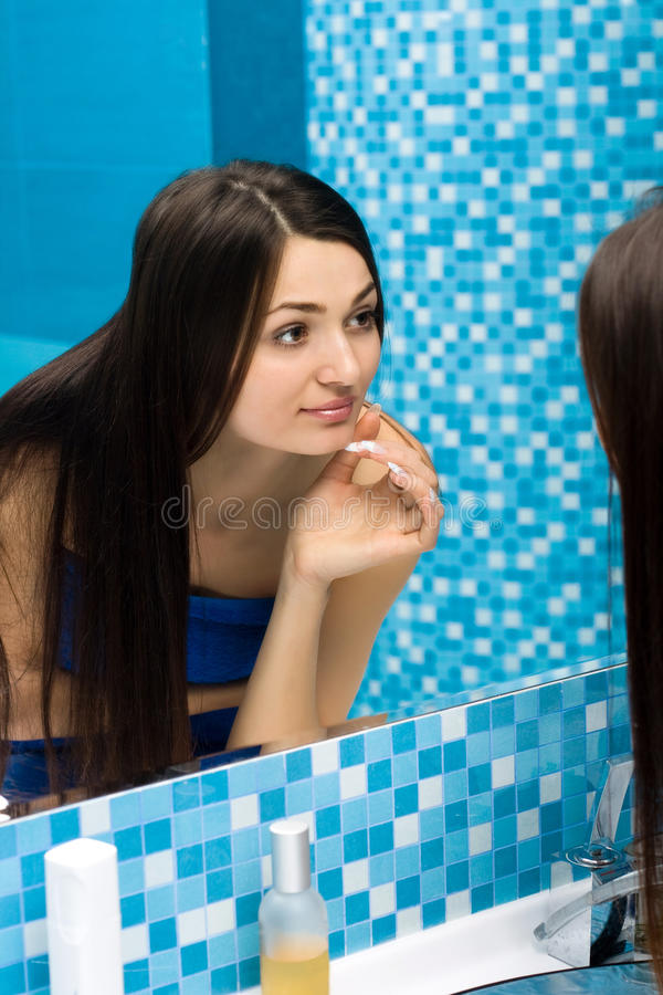 Woman in bathroom behind the mirror royalty free stock photo