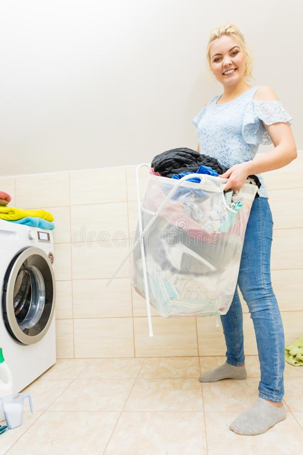 Woman carry big basket of dirty clothes laundry royalty free stock photos