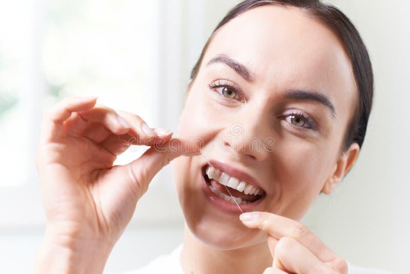 Woman In Bathroom Flossing White Teeth. Woman In Bathroom Flosses White Teeth royalty free stock photos