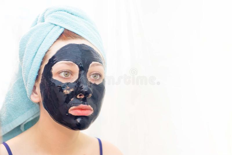 Cosmetic black mask. Woman in bathroom to put on cosmetic black mask on white background, right view. Sunny day. Put yourself in order royalty free stock photos