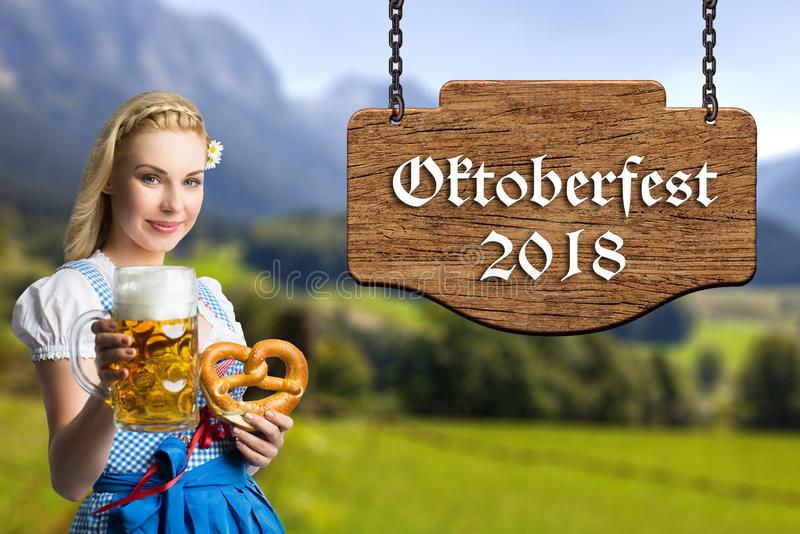 Woman in a bavarian dirndl with beer and pretzel and the text `Oktoberfest 2018` royalty free stock photo