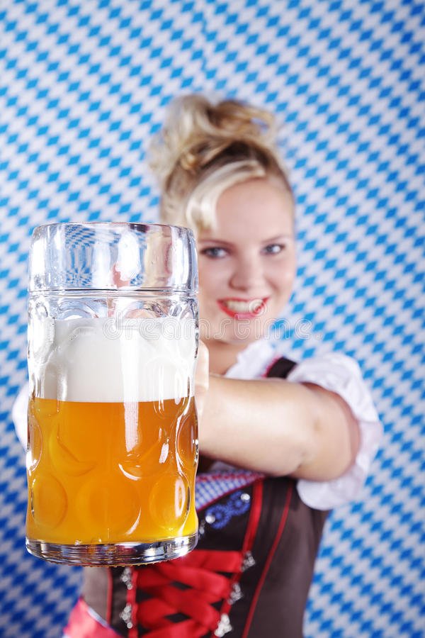 Woman in Bavarian outfit with beer. Beautiful woman in Bavarian outfit with beer royalty free stock photo