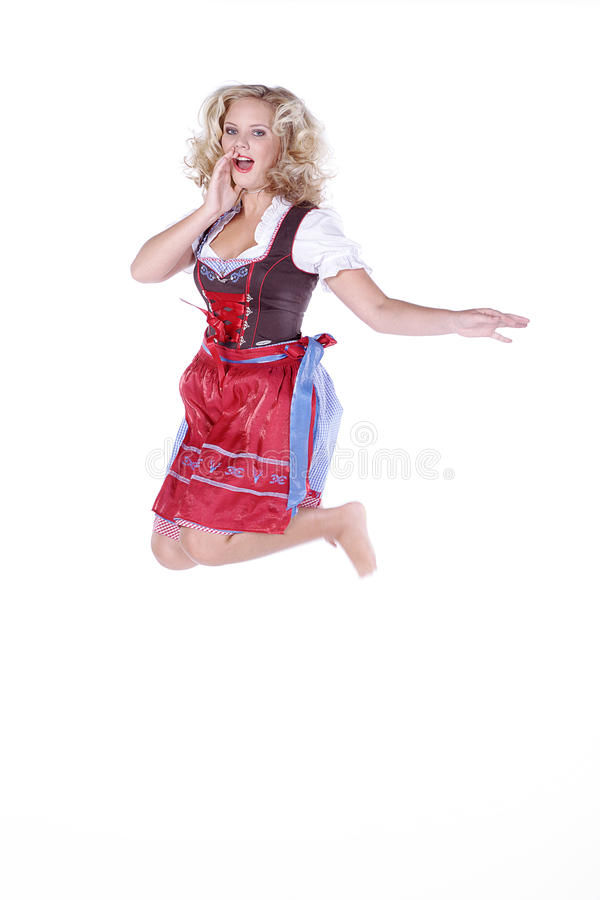 Woman in Bavarian outfit and jumps. Beautiful woman in Bavarian outfit and jumps royalty free stock images