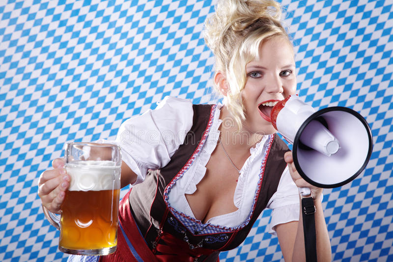 Woman in Bavarian outfit and megaphone and beer. Beautiful woman in Bavarian outfit and megaphone and beer royalty free stock photo