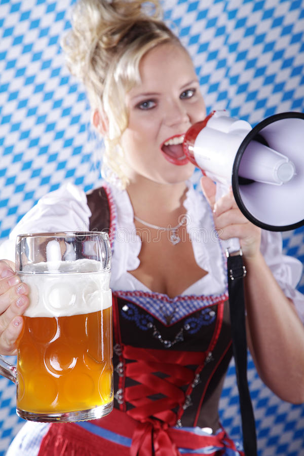Woman in Bavarian outfit and megaphone and beer. Beautiful woman in Bavarian outfit and megaphone and beer royalty free stock photography