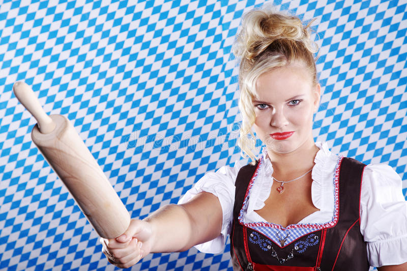 Woman in Bavarian outfit and rolling pin. Beautiful woman in Bavarian outfit and rolling pin stock images