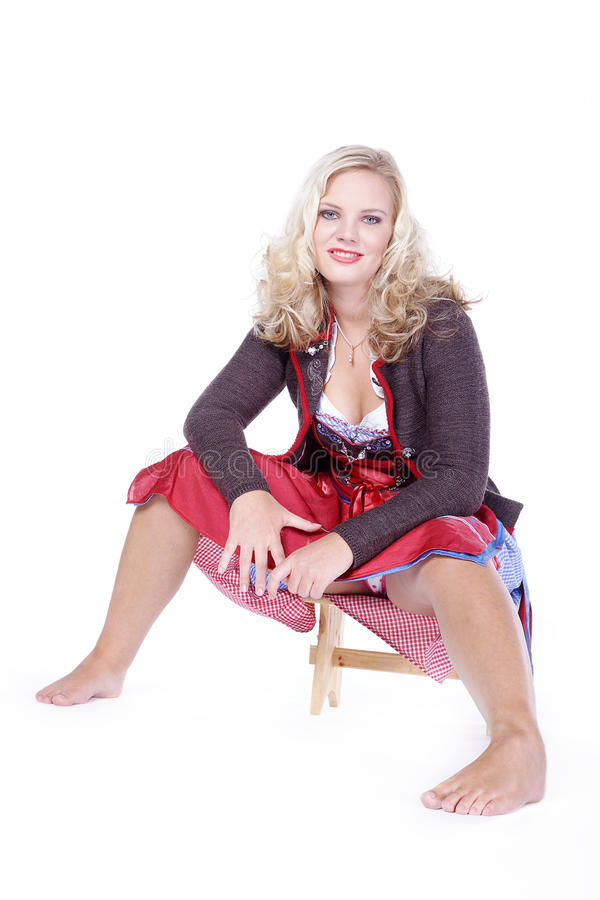 Woman in Bavarian outfit sitting on wooden stage. Beautiful woman in Bavarian outfit sitting on wooden stage royalty free stock photo
