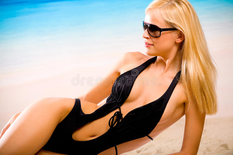 Woman on the beach. Tanned woman in bikini on the beach stock images