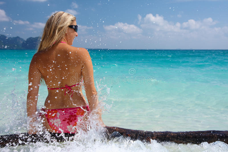 Woman on a beach. Caucasian blonde woman sitting on a log on a tropical island beach stock photography
